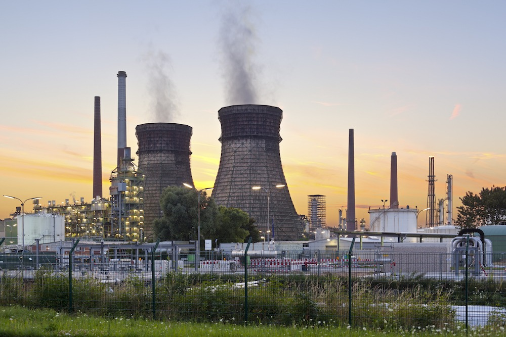 An oil refinery with two cooling towers and colorful evening sky.